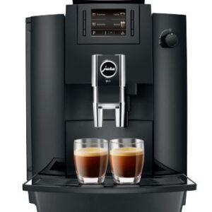 Kaffemaskine fra producenten JURA i versionen WE6, der fremstår i farven sort og med to nybryggede kopper kaffer